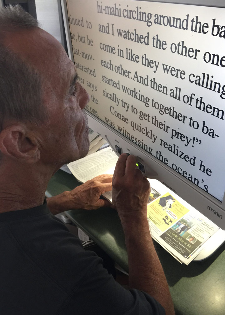 Man in front of screen that enlarges text so that he can read it