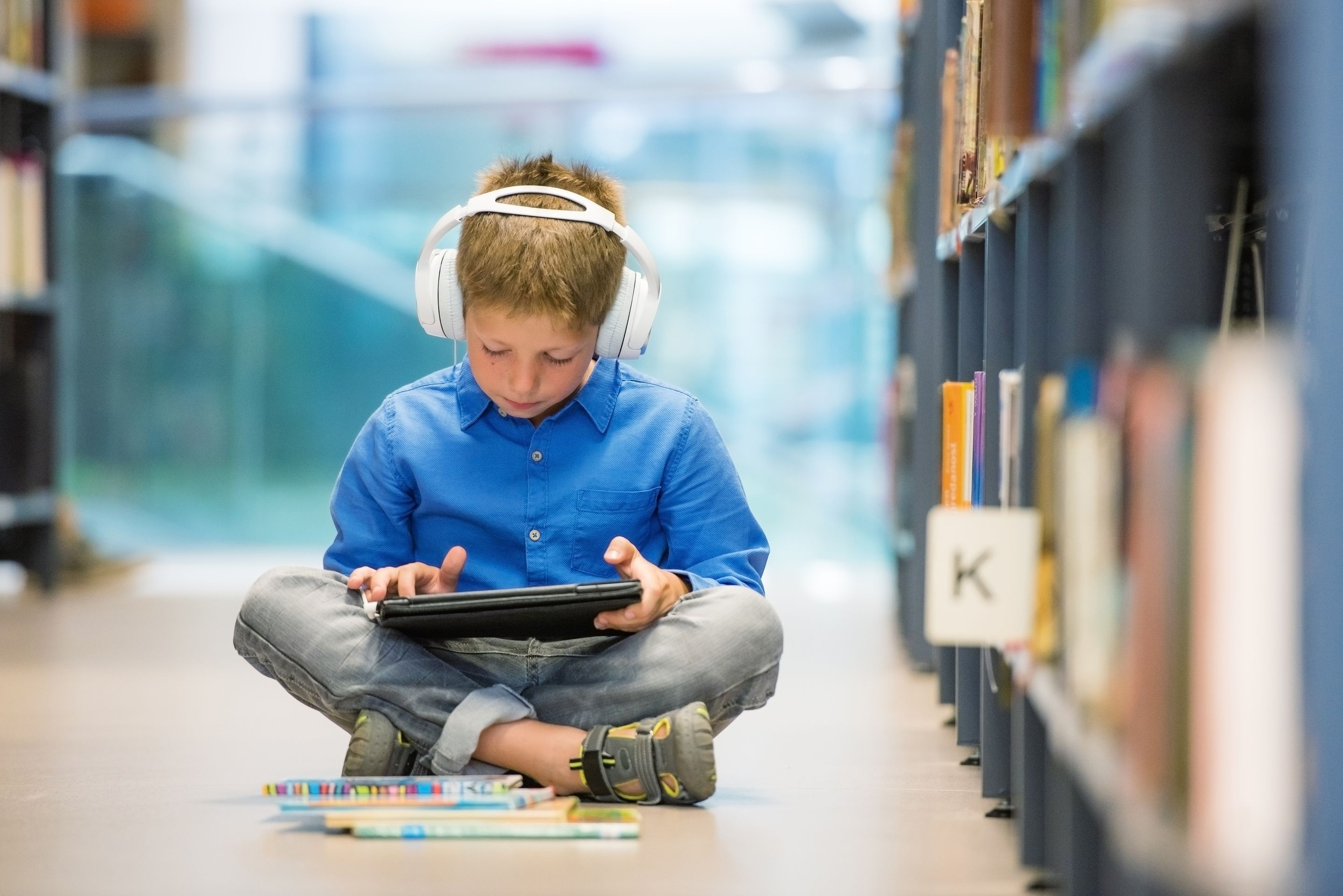 Young Boy sitting on floor in library looking at a tablet