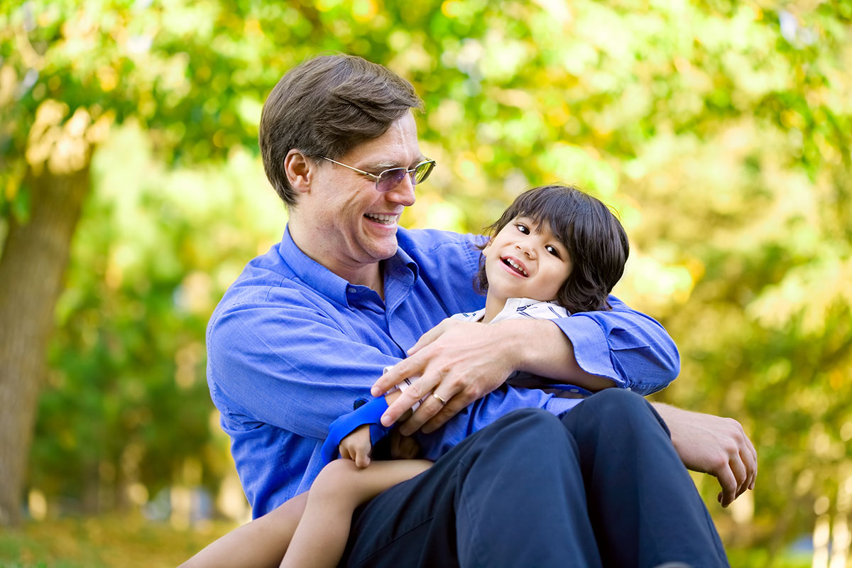 Smiling father holding smiling son who has cerebral palsy